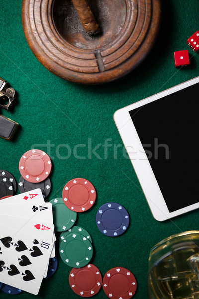 Ashtray, digital tablet, dice, casino chips and playing cards on poker table Stock photo © wavebreak_media