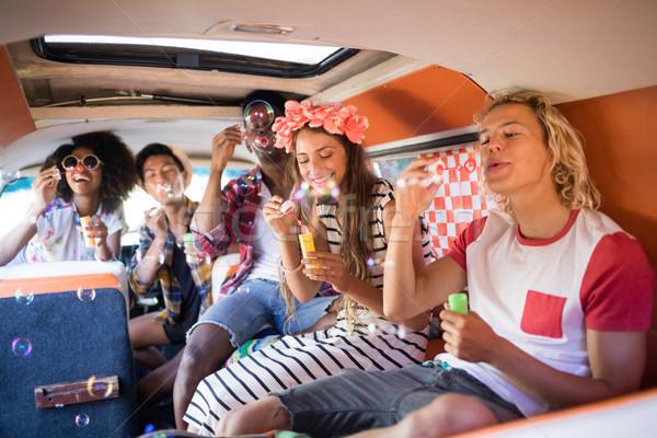 Happy friends blowing bubble wands in camper van Stock photo © wavebreak_media
