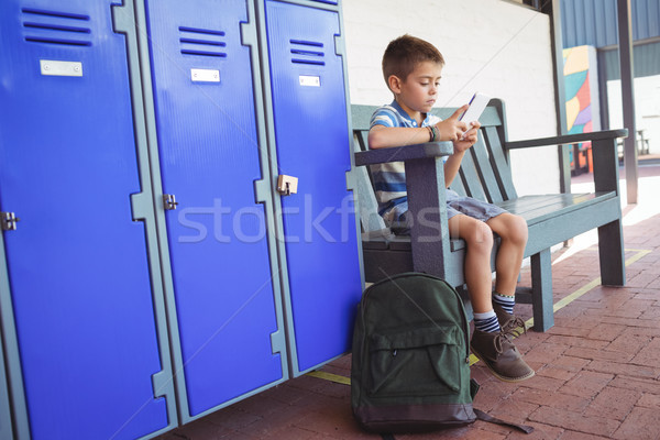 Fiú mobiltelefon ül pad folyosó iskola Stock fotó © wavebreak_media
