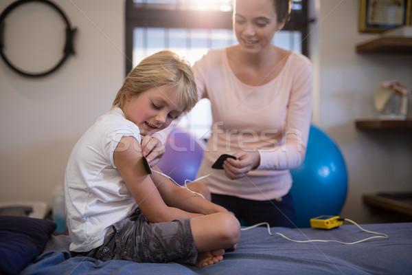 Female therapist positioning electrodes on arm of boy Stock photo © wavebreak_media