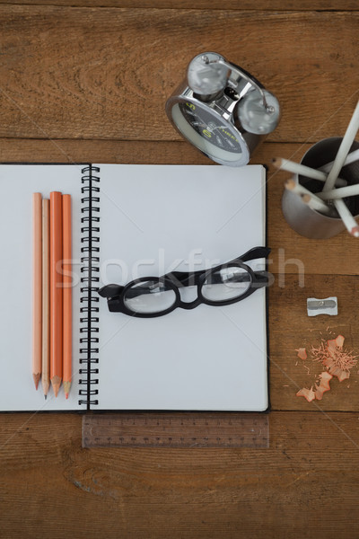 Alarm clock, book, pencil, scale, spectacles and sharpener on wooden table Stock photo © wavebreak_media