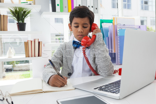 Businessman writing on book while talking on landline phone Stock photo © wavebreak_media