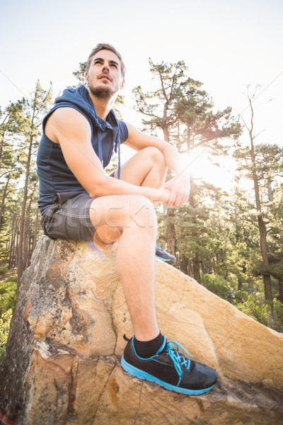 Young happy jogger sitting on rock and looking away Stock photo © wavebreak_media