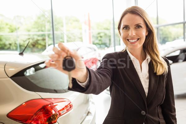 Smiling saleswoman holding car key Stock photo © wavebreak_media