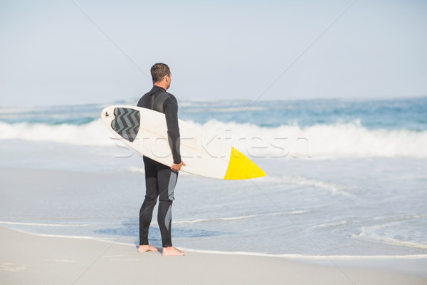 Rear view of man with surfboard standing on the beach Stock photo © wavebreak_media