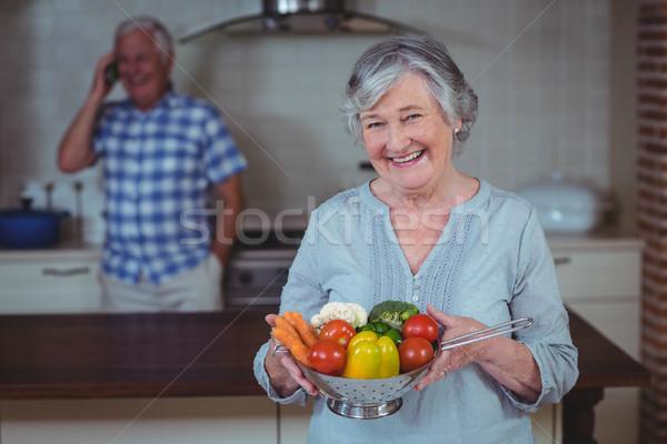 Senior woman holding colander with vegetables Stock photo © wavebreak_media