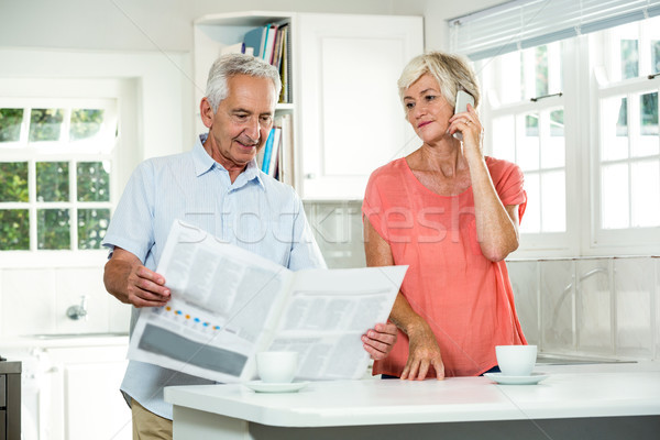 Senior man reading newspaper while woman using phone  Stock photo © wavebreak_media