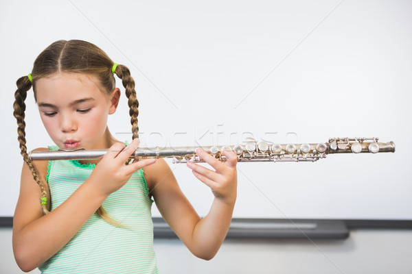 Schoolgirl playing flute in classroom Stock photo © wavebreak_media