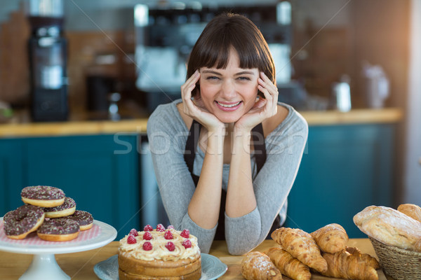 Portrait of waitress sitting at counter with sweet food on table Stock photo © wavebreak_media