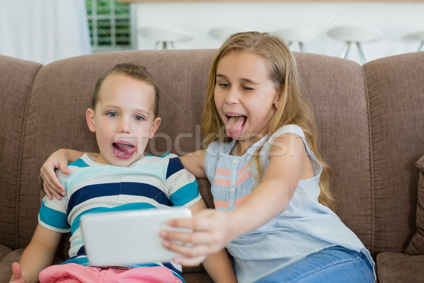 Sister and brother making funny faces while taking selfie from mobile phone Stock photo © wavebreak_media