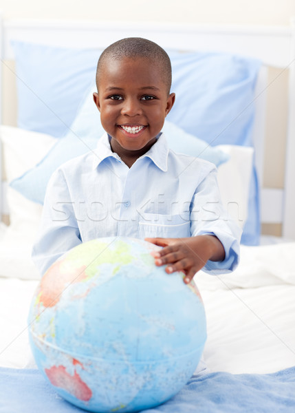 Cute little boy holding a terrestrial globe Stock photo © wavebreak_media