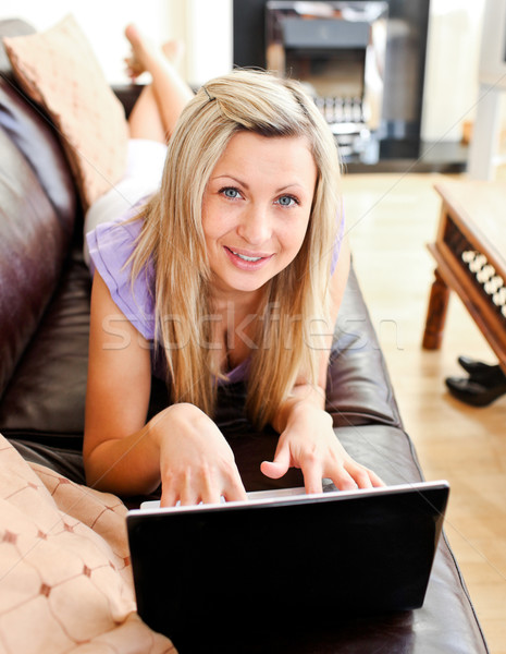 Nice woman lies on sofa and working with a laptop Stock photo © wavebreak_media