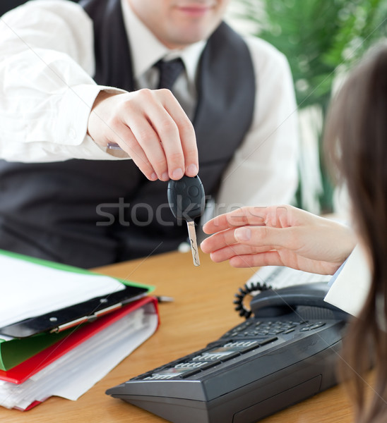 Stock photo: Young salesman giving car