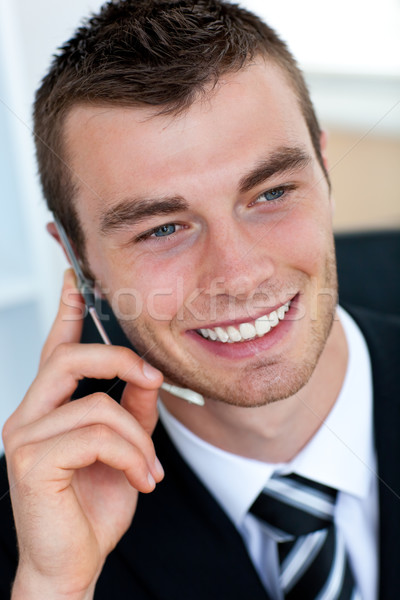 Stock photo: Pretty businessman using his mobile phone in office