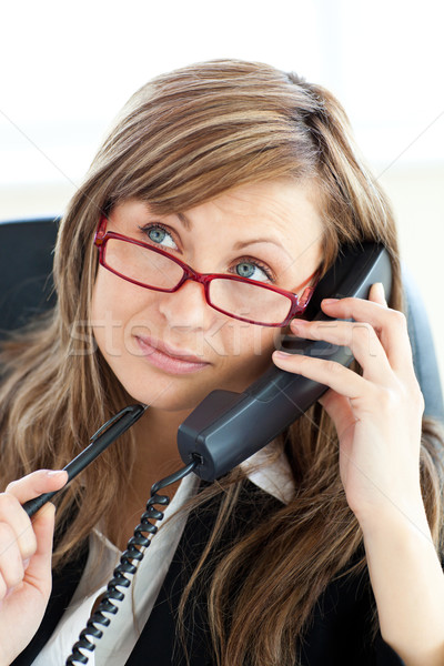 Pensive businesswoman talking on phone wearing glasses against white background Stock photo © wavebreak_media