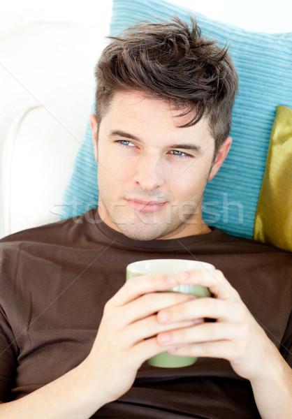 Charismatische jonge man beker sofa woonkamer Stockfoto © wavebreak_media