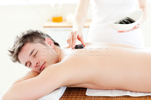 Charming young man receiving a massage with hot stone in a spa center Stock photo © wavebreak_media