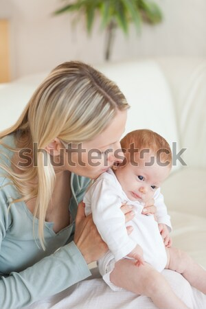 Adorable young mother kissing her baby sitting on a couch in the bedroom Stock photo © wavebreak_media