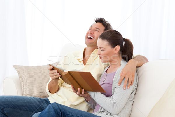 Uomo ridere guardando photo album fidanzata divano Foto d'archivio © wavebreak_media