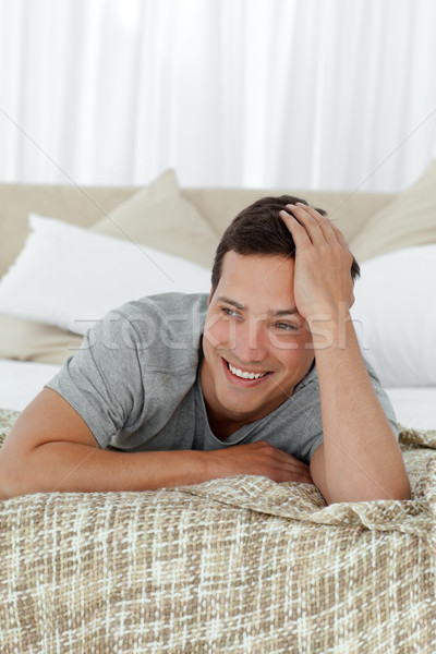 Happy man smiling lying on his bed Stock photo © wavebreak_media