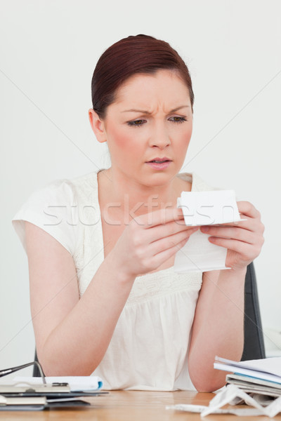 Stock photo: Young attractive red-haired female studying a receipt while sitting at a desk