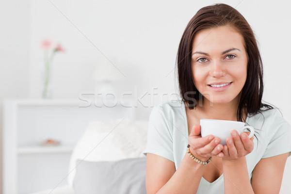 Beautiful dark-haired woman drinking tea while looking at the camera Stock photo © wavebreak_media