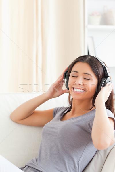 Aranyos nő fülhallgató csukott szemmel ül nappali Stock fotó © wavebreak_media