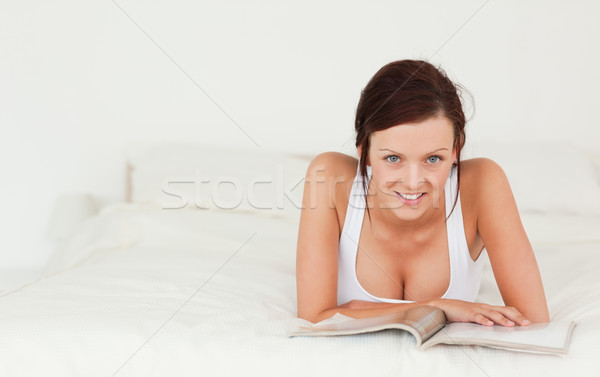 Portrait of a woman reading a magazine looking into the camera in the bedroom Stock photo © wavebreak_media
