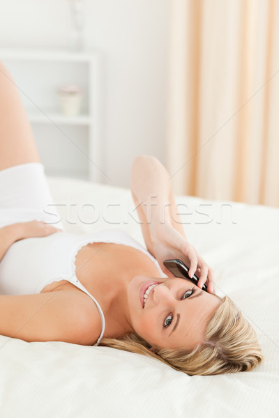 Portrait of a blonde woman making a phone call while lying on her bed Stock photo © wavebreak_media
