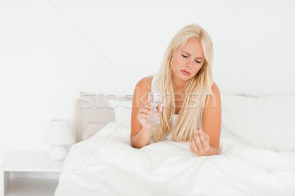 Woman taking her medication in her bedroom Stock photo © wavebreak_media