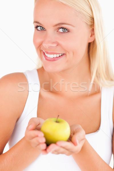 Glorious woman holding an apple in a studio Stock photo © wavebreak_media