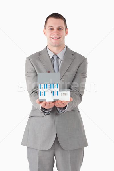 Portrait of a businessman showing a miniature house against a white background Stock photo © wavebreak_media
