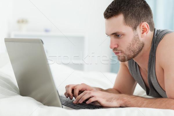 Odaklı adam dizüstü bilgisayar kullanıyorsanız göbek yatak odası bilgisayar Stok fotoğraf © wavebreak_media