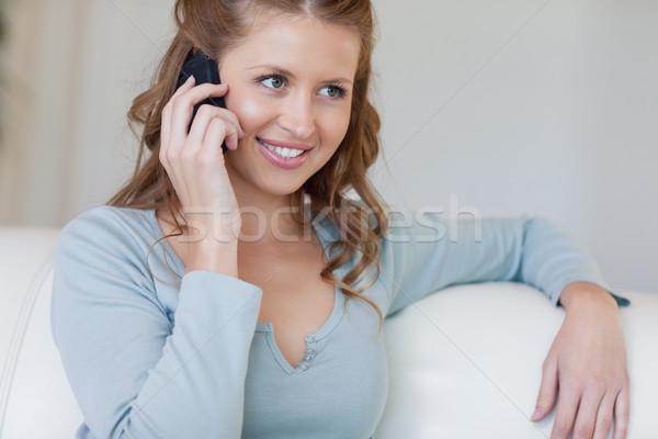 Młoda kobieta posiedzenia sofa słuchania rozmówca telefonu Zdjęcia stock © wavebreak_media