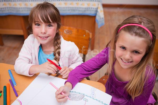 Cute schoolgirls drawing in a coloring book in a classroom Stock photo © wavebreak_media