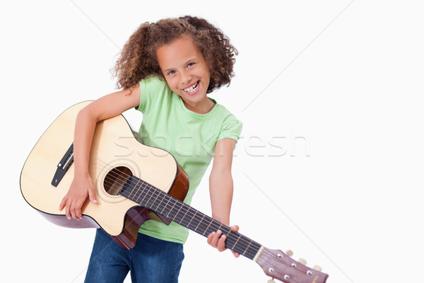 Happy girl playing the guitar against a white background Stock photo © wavebreak_media
