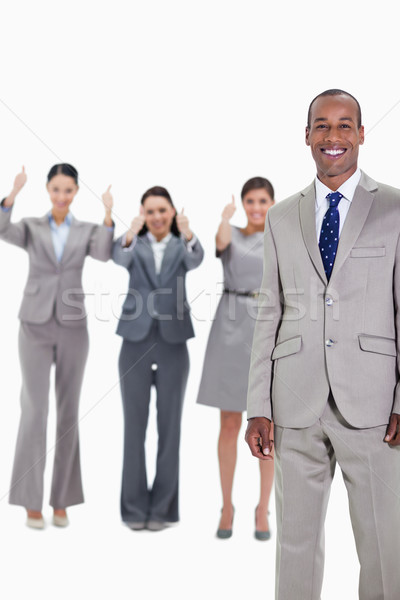Happy businessman with three approving co-workers in background with thumbs up Stock photo © wavebreak_media