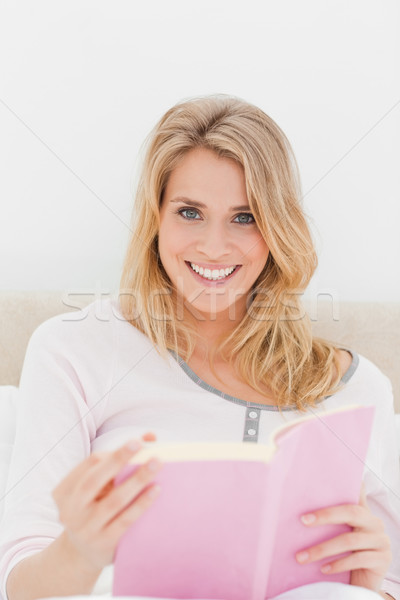 Stock photo: A close up shot of a smiling woman in bed as she holds a book in hand and is looking forward.