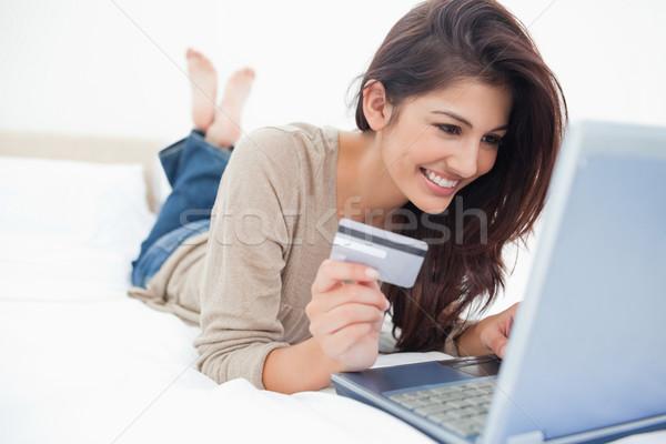 Mujer sonriente cama portátil tarjeta de crédito mano pies Foto stock © wavebreak_media