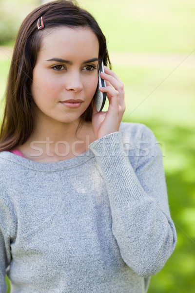Serious young woman calling with her cellphone while standing upright in a park Stock photo © wavebreak_media