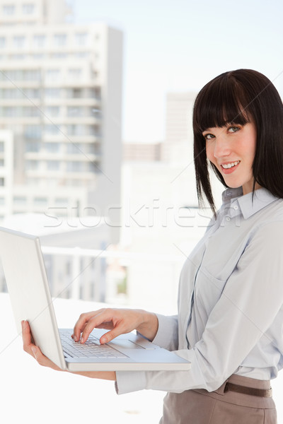 A smiling business woman looking at the camera as she uses her laptop Stock photo © wavebreak_media