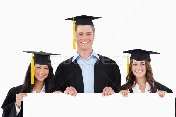 Drie afgestudeerden poster handen glimlach Stockfoto © wavebreak_media