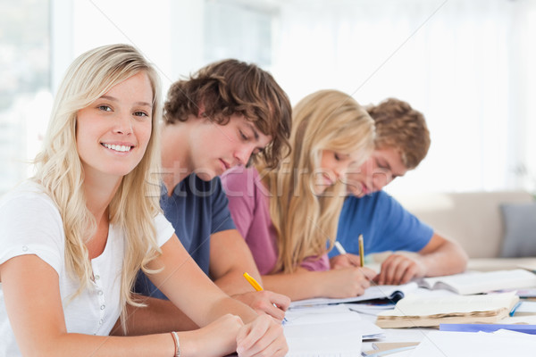 Smiling girl looking at the camera as her friends all study their homework  Stock photo © wavebreak_media