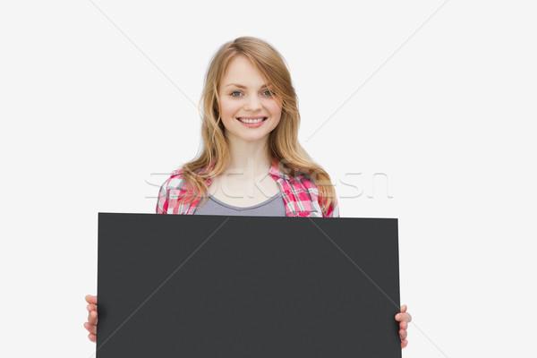 Nő néz kamera tart iskolatábla fehér Stock fotó © wavebreak_media