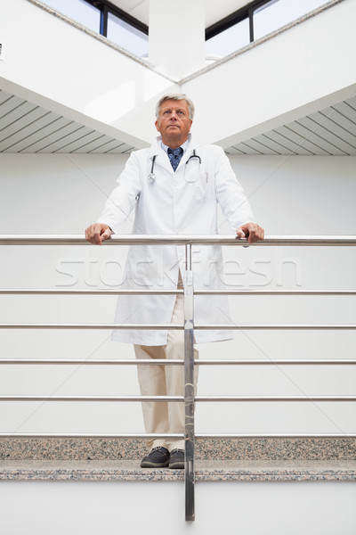 Thinking doctor stands at railing looking up in hospital corridor Stock photo © wavebreak_media