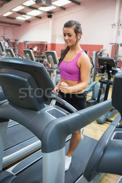 Woman jogging on a treadmill in a gym wearing black shorts and purple top concentrating Stock photo © wavebreak_media