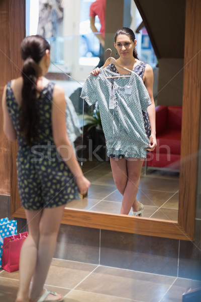 Woman is standing in front of the mirror with clothes in the changing room  Stock photo © wavebreak_media
