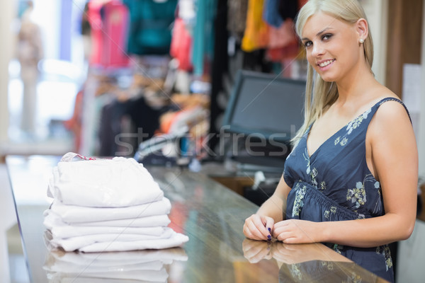 Smiling woman behind counter with folded clothes Stock photo © wavebreak_media