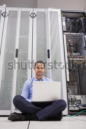 Man sitting on floor using laptop to check servers in data center Stock photo © wavebreak_media