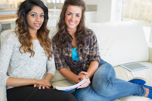 Two women sitting on a couch while writing on at a notepad in a kitchen Stock photo © wavebreak_media